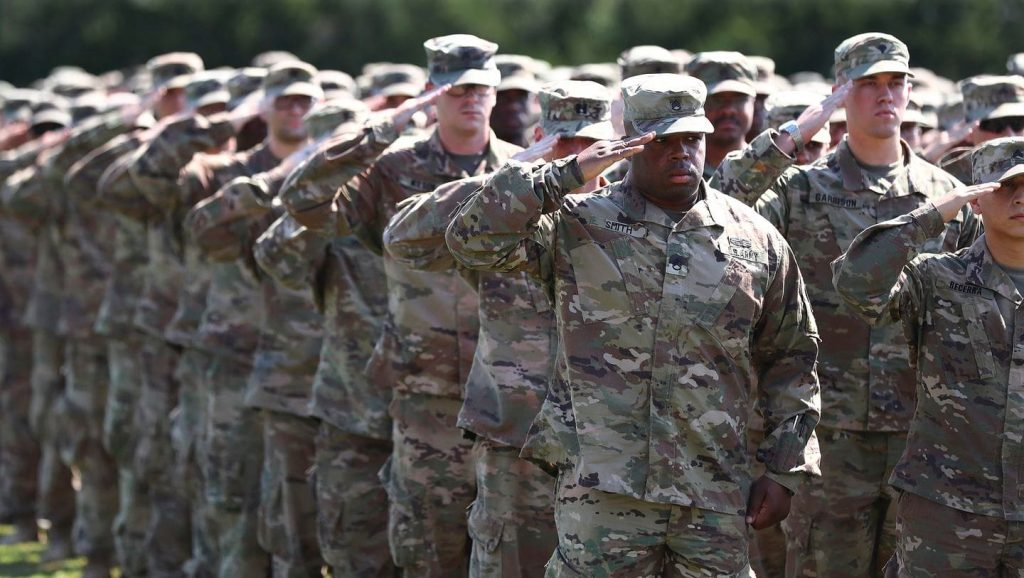 a line of soldiers stands in salute
