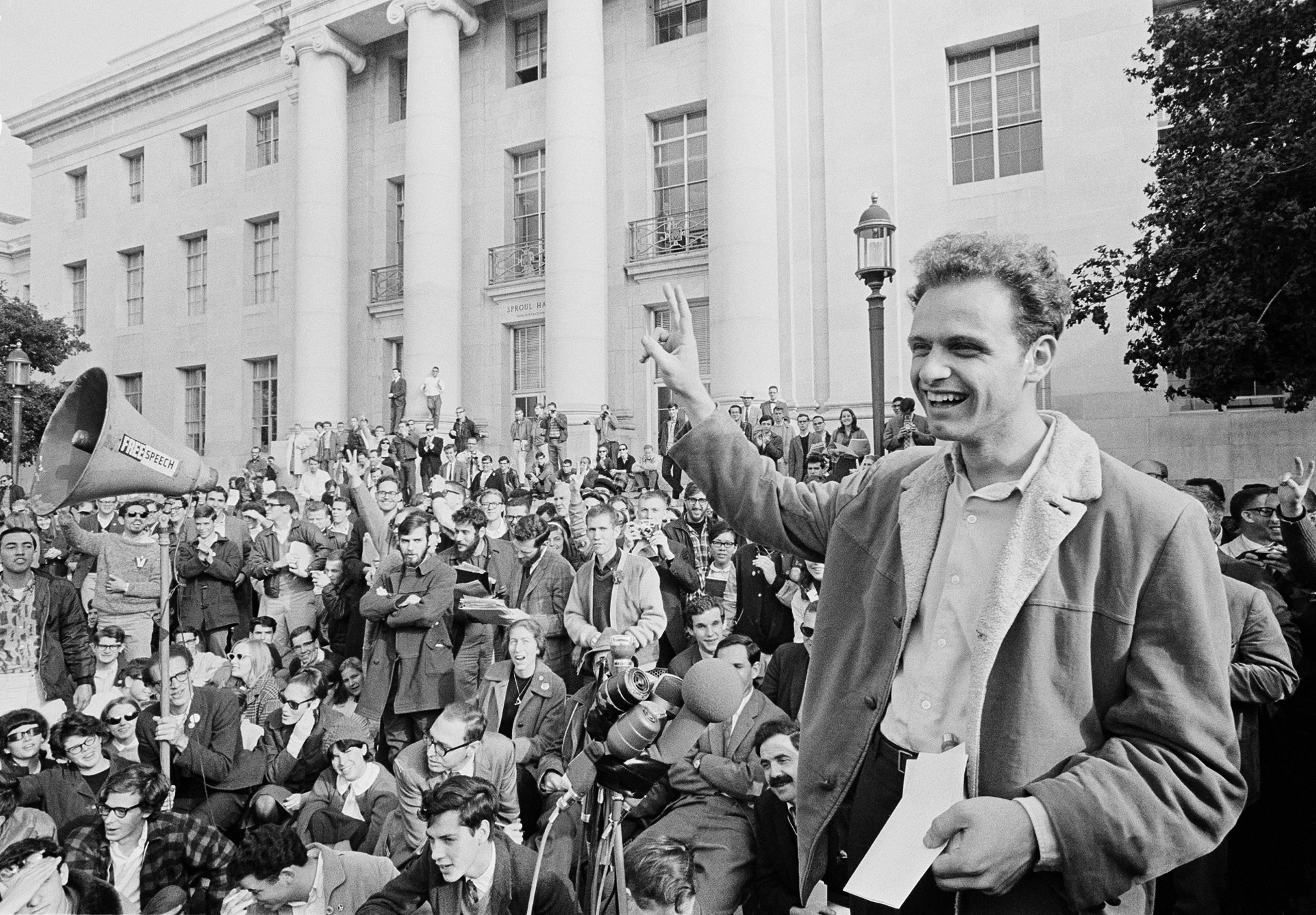 Mario Savio with his right hand raised in front of a crowd of students at UC Berkeley.