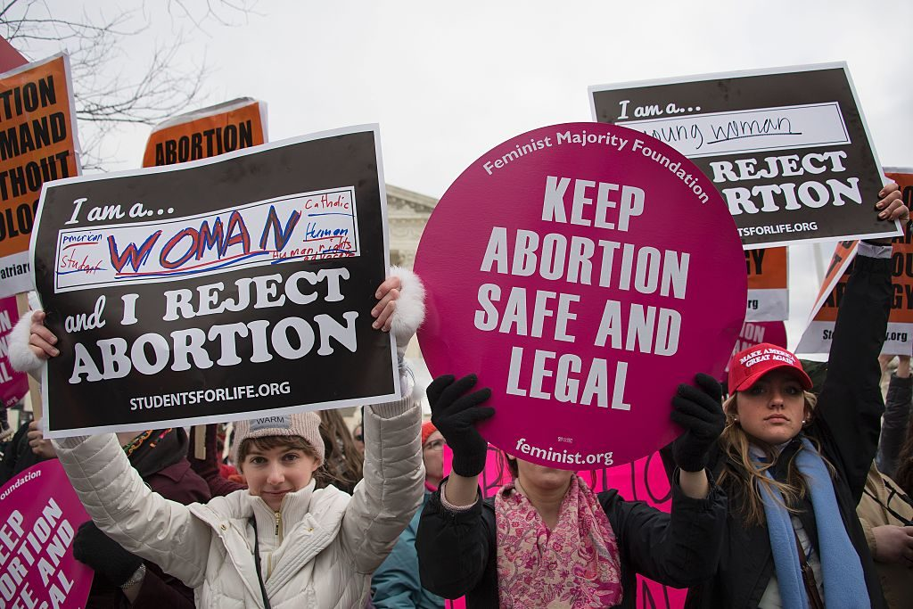 Pro-choice and pro-life protesters hold up opposing signs at a rally.