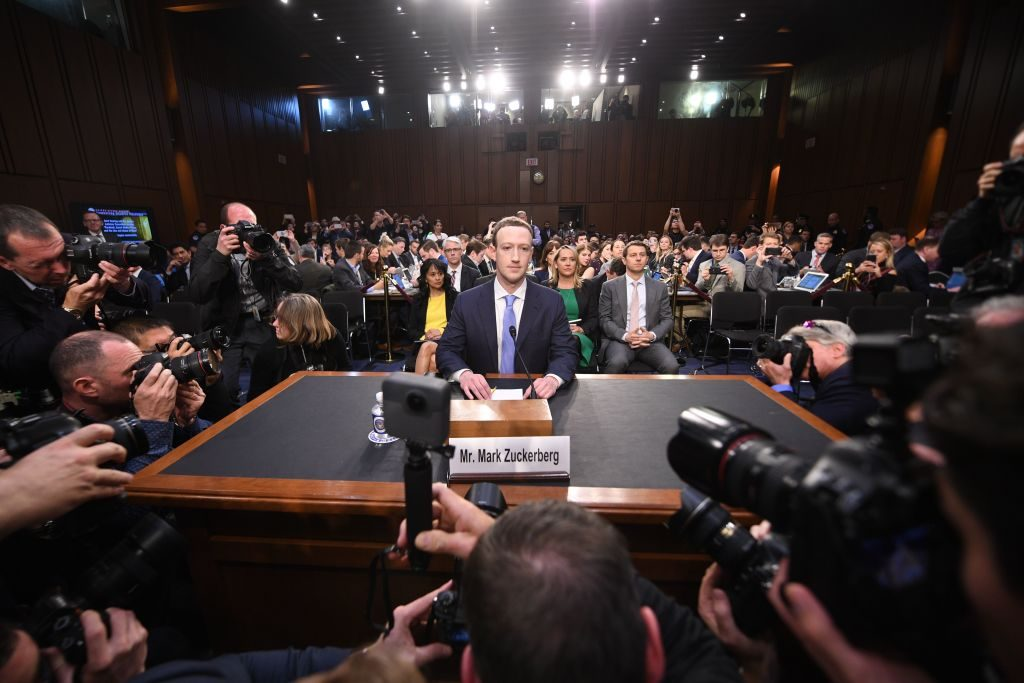 Facebook CEO Mark Zuckerberg sits surrounded by press at a congressional hearing.
