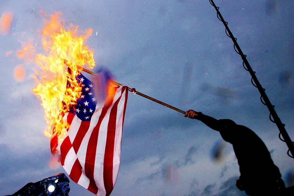 A man burns a U.S. flag in Copenhagen, Denmark to protest the arrival of U.S. President George W. Bush Tuesday July 5, 2005.