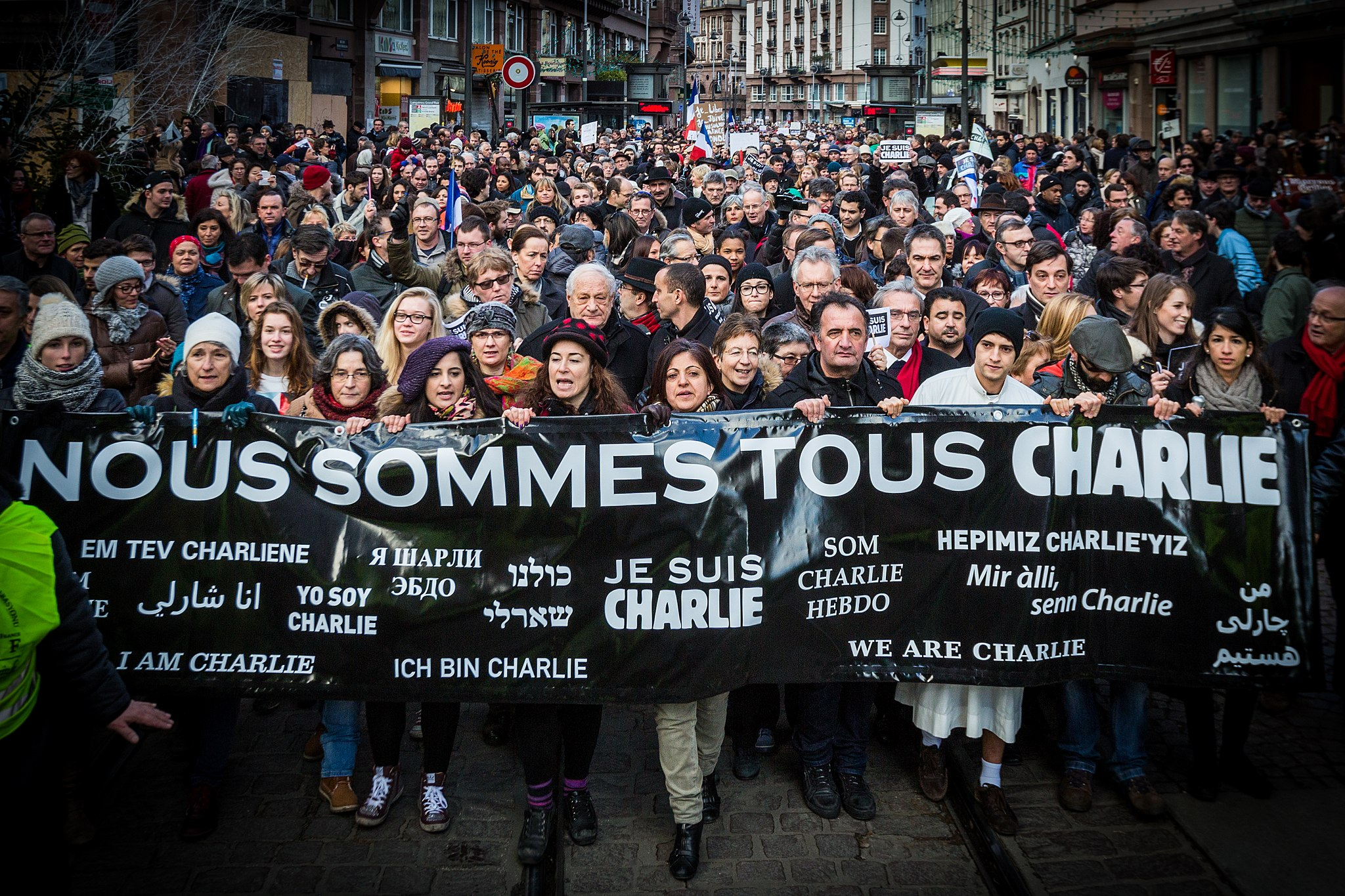 "A crowd of people demonstrate in Strasbourg, France, holding a sign that says ""We are all Charlie"" in many languages."