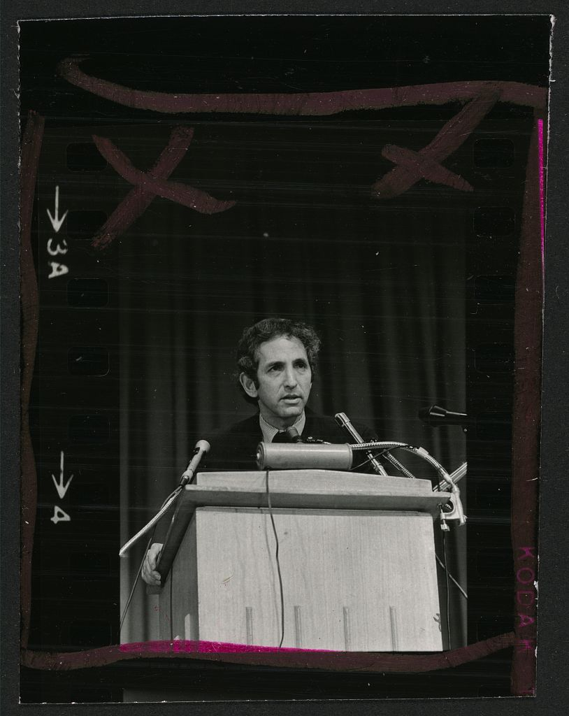 Whistleblower Daniel Ellsberg stands in front of a podium as he answers questions from the media.