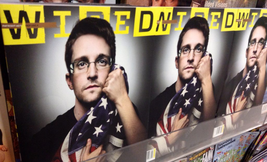 Edward Snowden appears on the cover of Wired Magazine, clutching a U.S. flag and looking off into the distance.