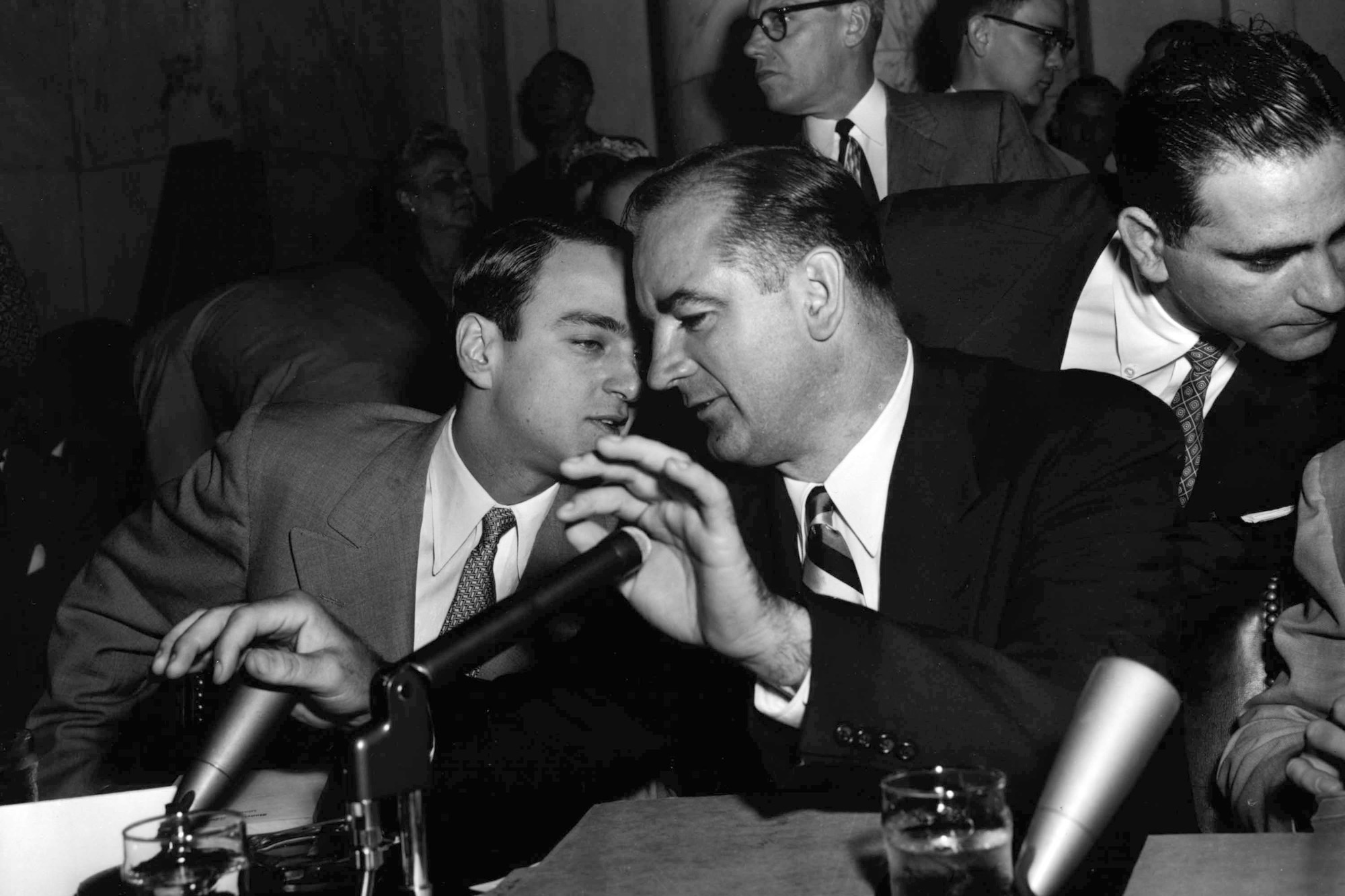 U.S. Sen. Joseph McCarthy holds both hands over microphones as he speaks to his chief counsel, Roy Cohn, during a hearing of the Senate Investigations Subcommittee in Washington April 22, 1954. The subcommittee was looking into McCarthy's dispute with top Army officials.