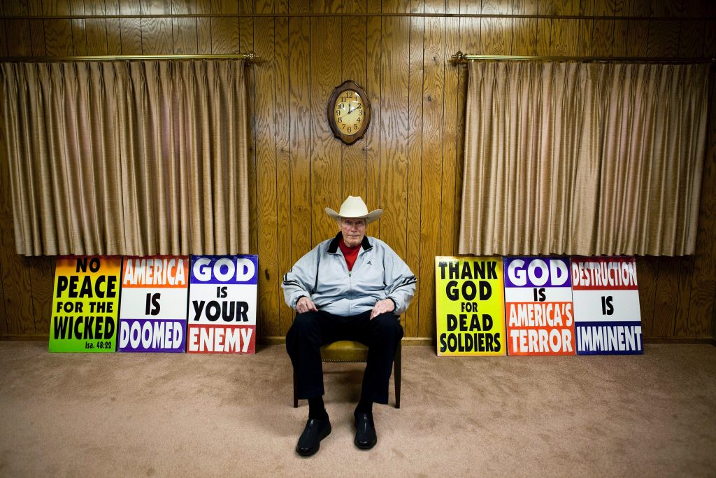 A Westboro Baptist Church member sits in between sets of protest posters in his living room.